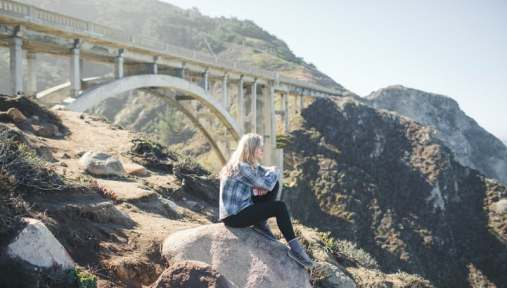 girl thinking with bridge in background